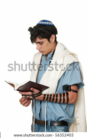 young Sephardic Jewish man in tallit and tefillin does morning prayers - stock photo