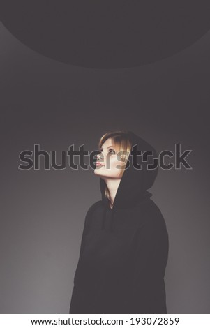 Young serene woman in black hood