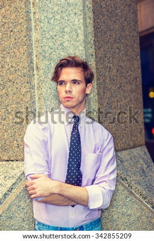Young serious American businessman in New York. Wearing light pink shirt, black, white polkadot necktie, a college student standing by column, crossing arms, thinking. Instagram filtered effect.  - stock photo