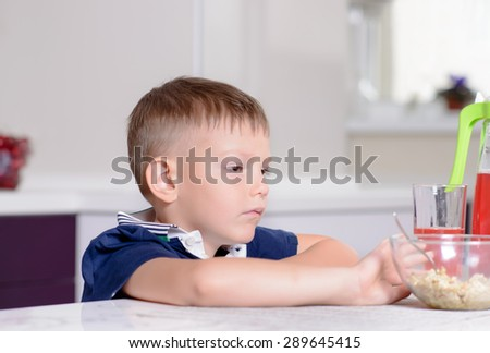 Young Serious Blond Boy Sitting at Kitchen Table Contemplating Bowl of Oatmeal Cereal and Red Juice at Breakfast