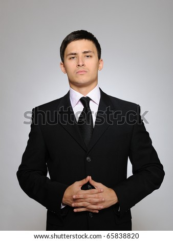 Young serious business man in black suit and tie. gray background