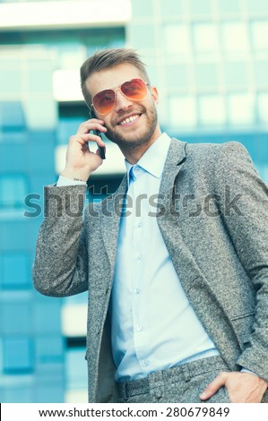 Young serious business man using his smart phone in front of his work place - stock photo