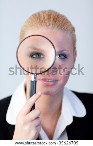 Young Serious Business woman looking through a magnifying Glass