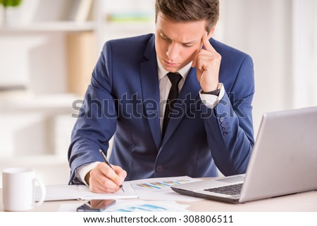 Young serious businessman is working in his office.