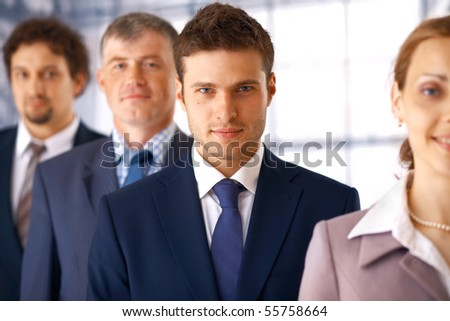 Young serious businessman standing in the row with his colleagues. - stock photo