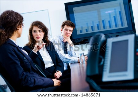 Young serious businesspeople talking in meeting room at office, phone and plasma TV. - stock photo