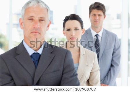 Young serious businesswoman accompanied by her manager and one colleague - stock photo