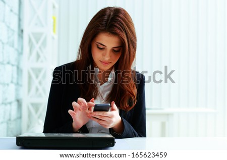 Young serious businesswoman typing on her smartphone in office - stock photo