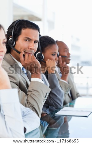 Young serious call center employee surrounded by his working team