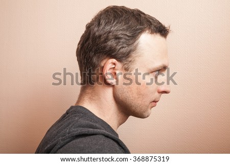 Young serious Caucasian man profile studio portrait over gray wall background - stock photo