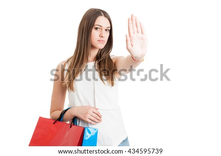 Young serious customer with shopping bags making a stop sign with hand as no more spending money on shopping concept isolated on white - stock photo