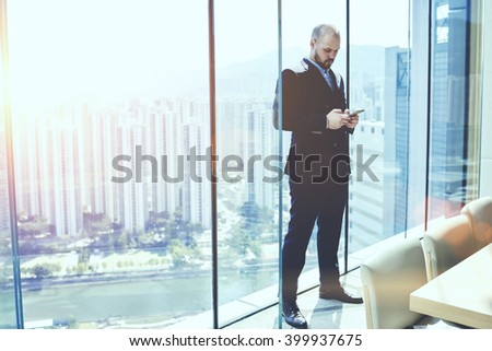 Young serious man CEO in suit is ordering on-line car for business trip via cell telephone, while is standing in conference room against window with view of New York city background with copy space - stock photo