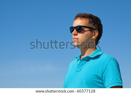 young serious man in sunglasses against blue sky - stock photo