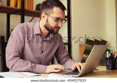 Young serious man with the glasses working on his laptop - stock photo