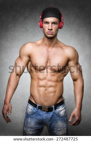 Young serious man with well trained body wearing a baseball cap and denim trousers - stock photo