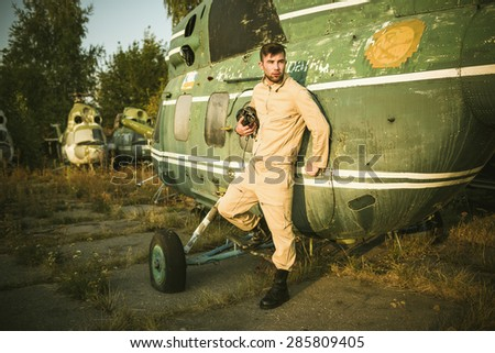 Young serious pilot posing near the helicopter - stock photo