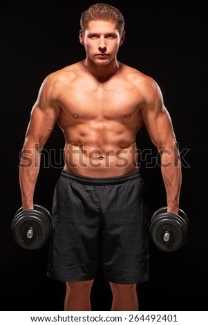 Young serious powerful muscular sportsman standing shirtless with black dumbbells in hands, with swollen blood veins, looking at camera, isolated on black background. Dressed in black shorts - stock photo