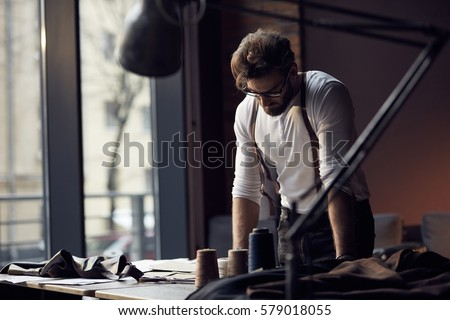 Young serious tailor with beard and glasses in white shirt with leather suspenders looking on drawing near wooden table with threads in amazing atelier with antique furniture and mannequin
