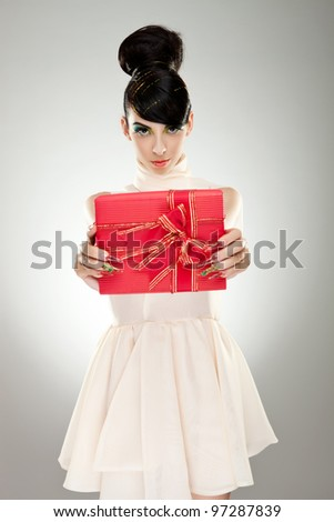 Young serious woman holding gift , giving it to the viewer - stock photo