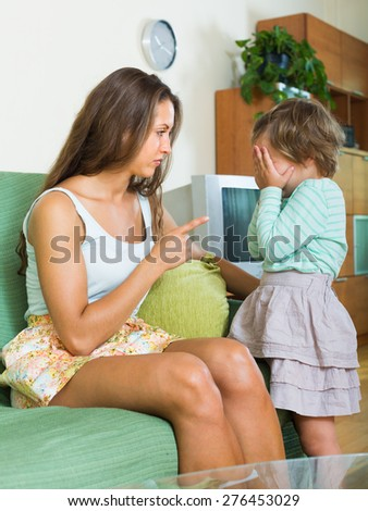 Young serious woman scolding crying child at home interior 