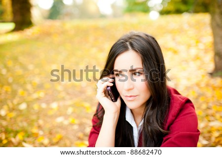 Young Serious Woman Talking on Cell Phone While in Park - stock photo
