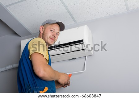 Young setup man installs the new air conditioner in the office. - stock photo