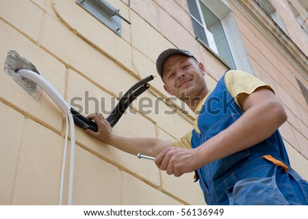 Young setup man paves the technological pipelines for a new air conditioner. - stock photo