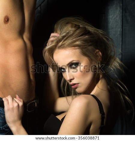 Young sexual couple of attractive blonde woman in bra touching and sitting near handsome man naked muscular chest and torso in studio on wooden background, square picture - stock photo