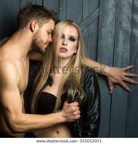 Young sexual couple of handsome serious man with bare muscular chest standing undressing pretty blonde woman standing and touching breast in studio, square picture - stock photo