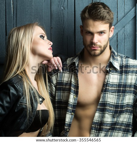 Young sexual couple of pretty blonde woman in leather jacket standing near handsome serious man in checkered shirt with bare muscular chest in studio on wooden background, square picture - stock photo
