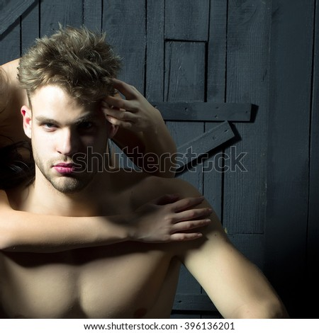 Young sexual handsome muscular man with bare torso sitting indoor touched by female hands on chest on wooden background, square picture - stock photo