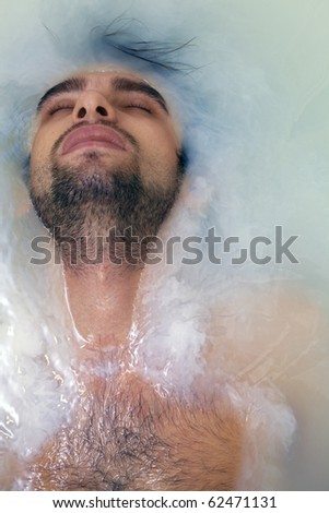 young sexual tanned naked guy in bath with muddy water - stock photo