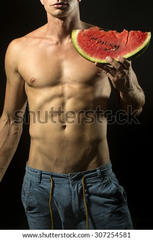 Young sexual undressed man in jeans with beautiful strong muscular body holding big juicy red water melon slice standing on black background, vertical picture - stock photo
