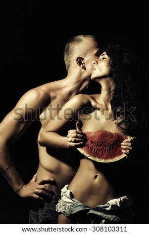 Young sexual undressed pair of pretty tan woman in jeans shorts holding big juicy red water melon slice and man with strong muscular beautiful body standing on black background, vertical picture
