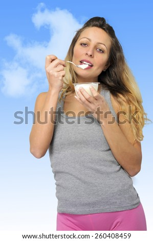 young sexy and attractive blond hair girl with spoon happy and fit eating natural cream yogurt in diet healthy nutrition and fitness concept on blue sky background - stock photo