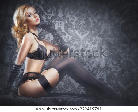 Young, sexy and beautiful blond girl in erotic lingerie over smoky background