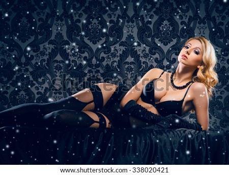 Young, sexy and beautiful woman in underwear in the bed over retro snowy background. - stock photo