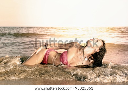 Young sexy and fit woman posing on the beach in Greece - stock photo