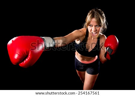young sexy angry fighter girl with red gloves fighting practice throwing aggressive punch training shadow boxing workout in gym isolated on black background  - stock photo