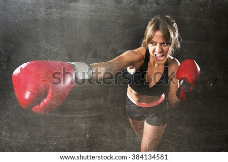 young sexy angry fighter girl with red gloves fighting practice throwing aggressive punch training shadow boxing workout in gym isolated on black dirty grunge background  - stock photo