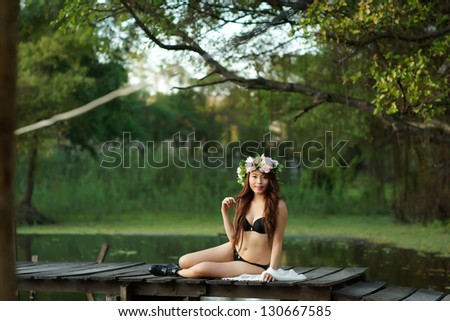 Young sexy Asian woman in black lingerie sitting on the wooden bridge outdoor.