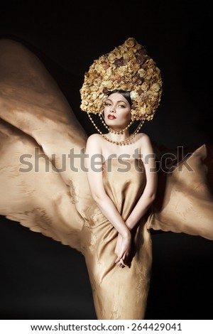 Young sexy beautiful woman in long dress with kokoshnik from roses - stock photo