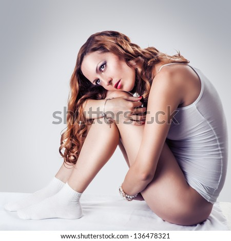 Young sexy beautiful woman in white cotton lingerie, socks, wristwatch and bracelets