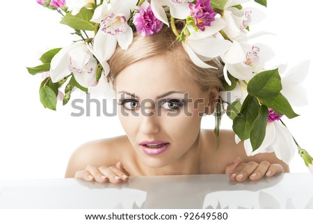 young sexy beautiful woman with naked shoulder and wearing a big crown of flower and leaves as spring queen, she is behind the table, has both hands on this and looks at left with an expression