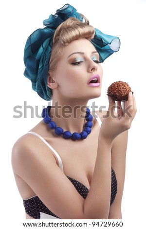 young sexy blond girl with blue head scarf and bra in pin up style eating a big chocolate  pastry - stock photo