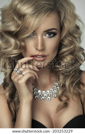 Young sexy blond woman in black lingerie  posing on studio  - stock photo