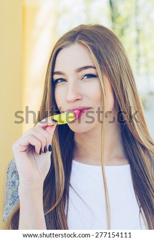 Young sexy blonde girl eating red ice cream in summer hot weather have fun and good mood  and smiling looking camera - stock photo