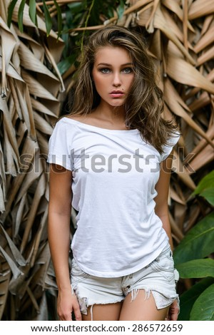 Young sexy blonde girl in white jeans shorts stay near tropical palms - stock photo