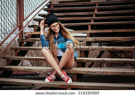 Young sexy blonde hipster woman posing for selfie and laughing. Wearing jeans jacket, hipster black hat and glasses. Lifestyle portrait - stock photo