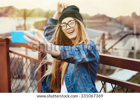 Young sexy blonde hipster woman posing for selfie and laughing. Wearing jeans jacket, hipster black hat and glasses. Lifestyle portrait bright with sun shine. - stock photo
